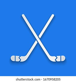 Paper cut Ice hockey sticks icon isolated on blue background. Paper art style. Vector Illustration