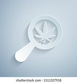 Paper cut Magnifying glass and medical marijuana or cannabis leaf icon isolated on grey background. Hemp symbol. Paper art style. Vector Illustration