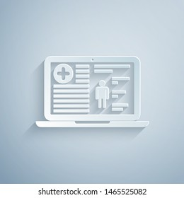 Paper cut Medical clinical record on laptop icon isolated on grey background. Health insurance form. Prescription, medical check marks report. Paper art style. Vector Illustration