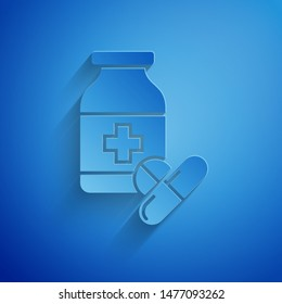 Paper cut Medicine bottle and pills icon isolated on blue background. Bottle pill sign. Pharmacy design. Paper art style. Vector Illustration