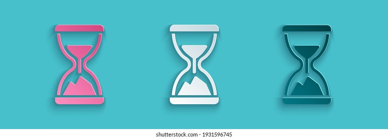Paper cut Old hourglass with flowing sand icon isolated on blue background. Sand clock sign. Business and time management concept. Paper art style. Vector
