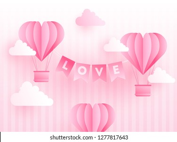 Paper origami of heart shapes hot air balloons with love lettering on cloudy stripe background. Valentine's Day celebration poster or template design.