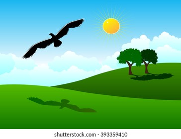 park. Green hills, couple of trees and a black bird against the blue sky and clouds