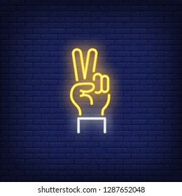 Peace neon sign. Glowing hand with two fingers in piece gesture on brick wall background. Vector illustration can be used for gesturing, communication, chatting