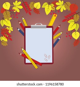 Pencils, writing pad, clips and ruler on brown background with autumn colourfull leaves and berries. Autumn learning concept. Back to school