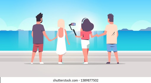 people group on beach using selfie stick taking photo on smartphone camera summer vacation concept rear view friends standing together seaside sea holiday ocean travel full length horizontal