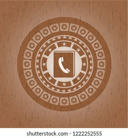 phonebook icon inside badge with wood background