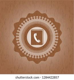 phonebook icon inside wooden emblem