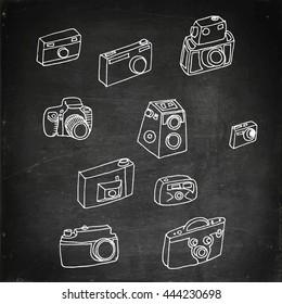 Photo cameras set. Hand drawn vector stock illustration. Chalk board drawing.