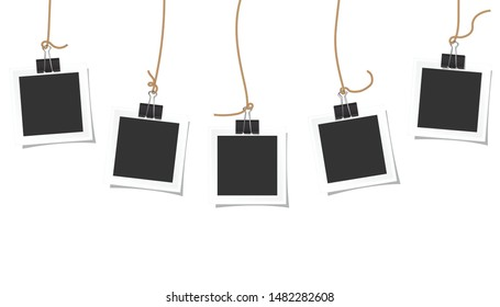 Photo square frames hanging on a black paper clip and beautiful shadow on white background.