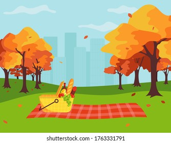 A picnic concept in a city park in the fall. Basket and picnic blanket on the background of autumn trees and the city. Cartoon vector illustration in flat style.