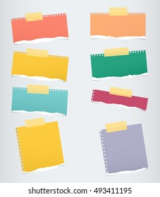 Pieces of colorful ruled torn note paper with yellow adhesive, sticky tape stuck on grey background