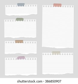 Pieces of torn white blank lined note paper with colorful sticky tape on gray background