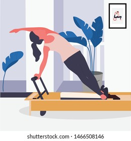 A pilates girl working out with pilates reformer equipment