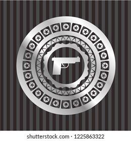pistol icon inside silvery badge