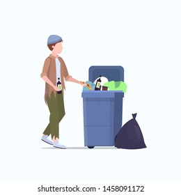 poor man beggar holding bottle of alcohol tramp searching food and clothes in trash can on street homeless jobless unemployment poverty concept white background full length