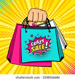 Pop art background with female hand holding bright shopping bags and Crazy sale speech bubble with stars and halftone. Vector colorful hand drawn illustration in retro comic style.