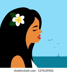 Portrait of beautiful tanned black-haired girl with plumeria flower in hair. Sea landscape. Profile view