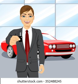 portrait of young handsome automobile salesman holding the key of a brand new red car into car showroom