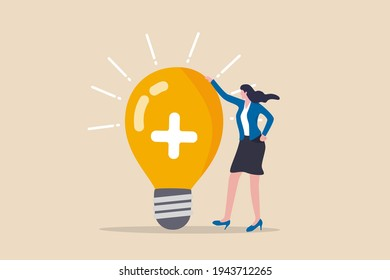Positive thinking, optimistic bring success to work and living, inspiration and happiness in work concept, cheerful businesswoman standing with bright lightbulb idea with positive sign.