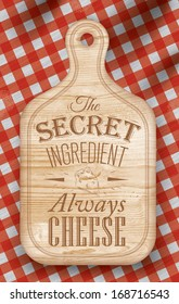 Poster with bread cutting loft wood color board lettering the secret ingredient always cheese on a red checkered tablecloth.