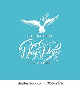 Poster with hand lettering of International Day of Peace. Vector hand drawn illustration of dove with a palm branch on blue background. Holiday card with calligraphy.