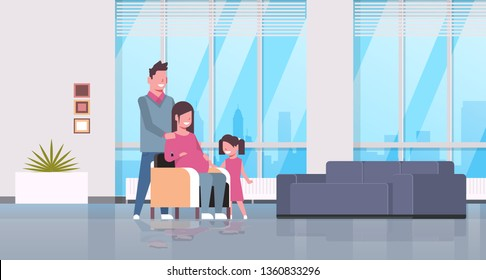 pregnant woman with husband and daughter happy family at home girl touching mother belly pregnancy and motherhood concept living room interiorfull length horizontal