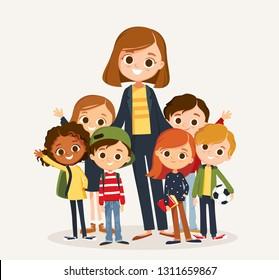 Pretty teacher standing with pupils. Classmates portrait with teacher. Elementary school.