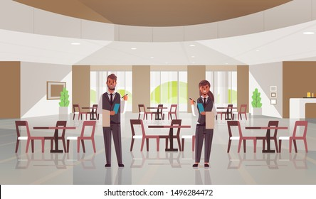 professional waiters couple standing together man woman restaurant workers in uniform holding notepad and towel taking order concept modern cafe interior flat full length horizontal
