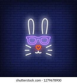 Rabbit neon sign. Easter bunny face in sunglasses with heart shaped nose on brick wall background. Vector illustration in neon style for topics like spring, Easter, celebration