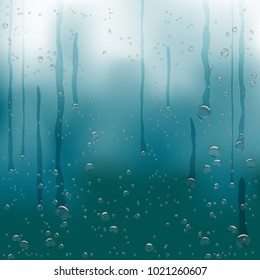 Rain water drops flow down on dark blue background. Beautiful fresh aqua bubble shape natural droplets backdrop. Rain bubbles template on a surface