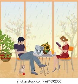 Rainy day. A young couple sitting and enjoying the living room. Girl  reading a book. The young man looks at a laptop