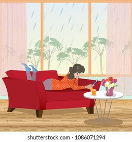 Rainy spring day. The girl lies and relaxed on the couch and is listening to music on the mobile phone