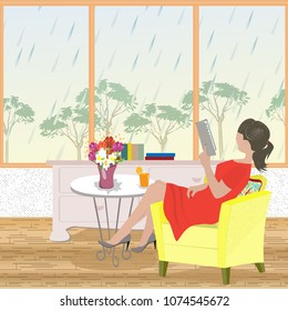 Rainy spring day. The young woman in a red dress sits relaxed in her armchair and reads the book
