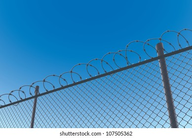 Realistic cartoon illustration of a chain link fence topped with barbed wire, viewed from a low angle with copy space.