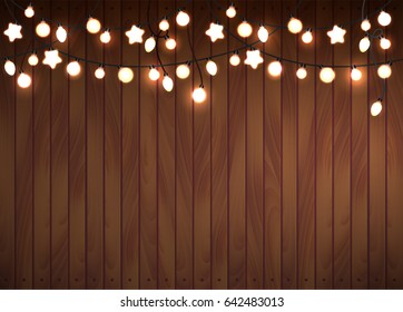 Realistic luminous garland Background. Garland is seamless border. Christmas decoration. Wood background.