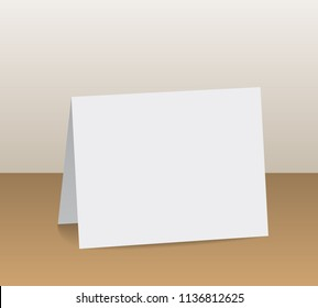 Realistic white blank folded paper card standing on wooden table top - vector