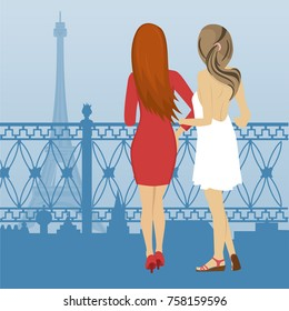 Rear view of two women standing on the embankment and look at the Eiffel Tower in Paris