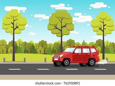 Red off-road car rides along  suburban road against the background of green forest and a blue sky with clouds.