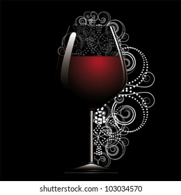 Red wine in glass on black back.