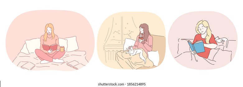Relaxation with book at home, lazy bedding time concept. Young positive women in comfortable home clothing staying in bed, reading books and relaxing with cat and hot drink at home
