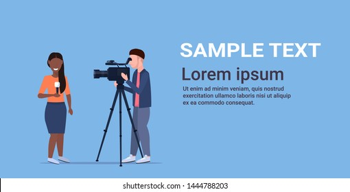 reporter man with african american woman journalist presenting live news operator using video camera on tripod recording correspondent with microphone movie making concept horizontal copy space