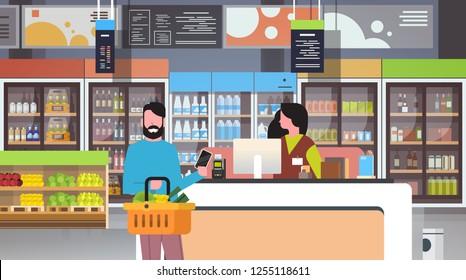 retail woman cashier at checkout supermarket man customer holding basket food paying smartphone shopping concept grocery market interior flat horizontal