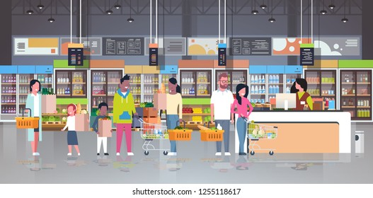 retail woman cashier at checkout supermarket mix race customers holding basket with food standing line queue shopping concept grocery market interior flat horizontal