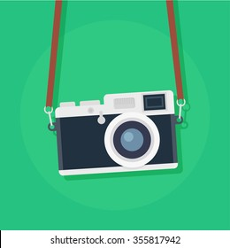 Retro camera in a flat style on a colored background. Old camera with strap.