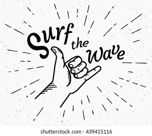 Retro grunge black and white illustration of human hand doing surfer shaka insignia with surf the wave handmade text. Hipster shaka label with sunburst rays engrave isolated on white background.