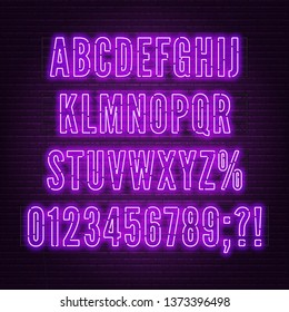 Retro purple neon alphabet with numbers on brick wall background.