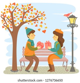 Romantic couple sitting on a bench and giving each other gifts for Valentine's Day.