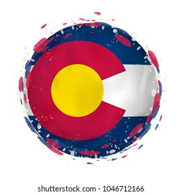 Round grunge flag of Colorado US state with splashes in flag color. Vector illustration.