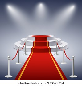 Round podium with red carpet and barrier rope in glow of spotlights